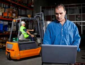 Man Working on Laptop in Warehouse